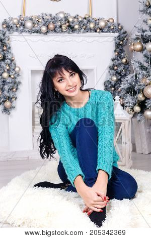 Beautiful young brunette woman with long hair sitting on a floor indoors in a christmas interior. Looking at camera.