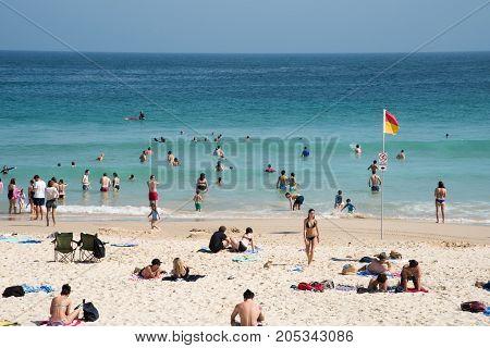 SYDNEY,NSW,AUSTRALIA-NOVEMBER 21,2016: Swimming, wading, surfing and sunbathing on the Pacific Ocean coast at Bondi Beach in Sydney, Australia.