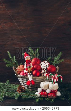 Doll Sitting In A Basket With Fir Tree Branches, Red Balls And S