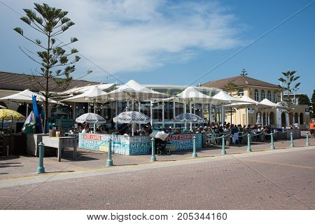 SYDNEY,NSW,AUSTRALIA-NOVEMBER 21,2016: The Bucket list sidewalk cafe with people on the Bondi Beach foreshore in Sydney, Australia
