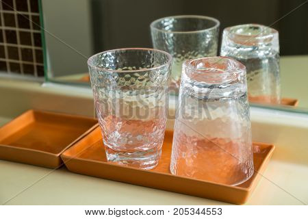 two drinking glasses in brown ceramic tray