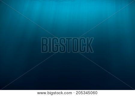 Water texture in underwater and sun rays. Blue ocean in underwater