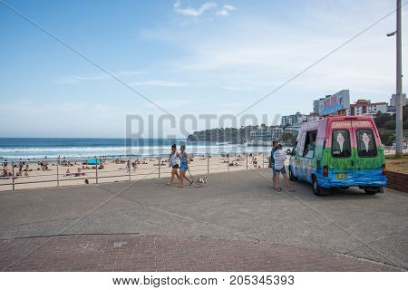 SYDNEY,NSW,AUSTRALIA-NOVEMBER 21,2016: Bondi Beach foreshore with girls walking dog and couple at Ice-cream truck vendor on the Pacific Ocean coast in Sydney, Australia.