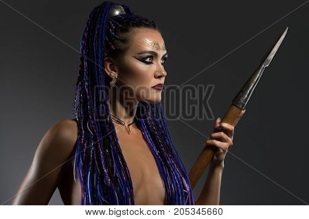 Sexy resolute horsewoman with blue dreadlocks topless holding a spear in her hand cropped view in profile on gray background