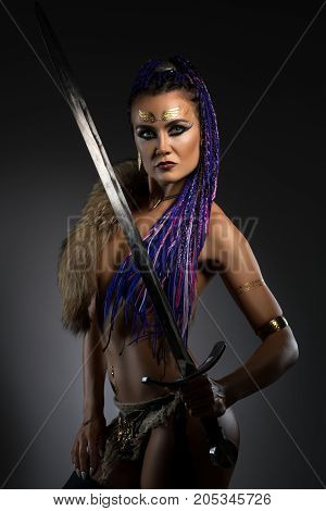 Sexy resolute horsewoman with African braids hairstyle, temporary gold tattoo on her face and bright makeup in original leather underwear holding a sword in her hand portrait on dark background cropped shot