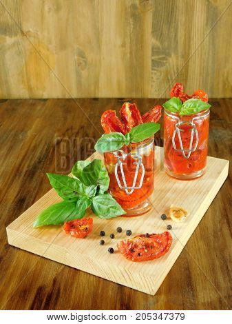 Sun-dried tomatoes with garlic, basil and spices on a wooden board