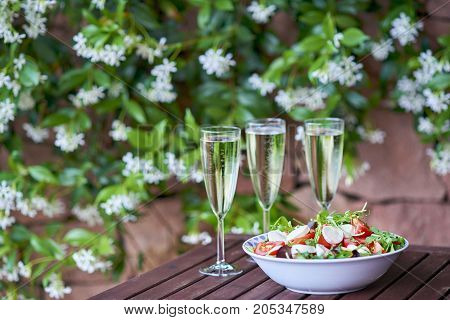 Three glassed of champagne and fresh salad