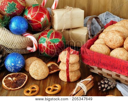 Biscuits with cinnamon in a wicker basket surrounded by present boxes and Christmas attributes on a wooden background