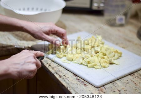 Hands Cutting Canned Artichokes