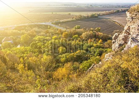 Seasonal natural outdoors scene in sunset - rocks colorful trees village road and fields. Beauty in nature. Vibrant colors.