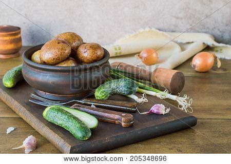 Natural food. Baked potatoes in a round wooden bowl, fresh cucumber, garlic, fork and knife on a cutting board, near a napkin and onion.