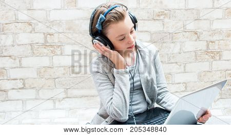 Portrait Of A Teenager Girl Who Listens To Music In Headphones