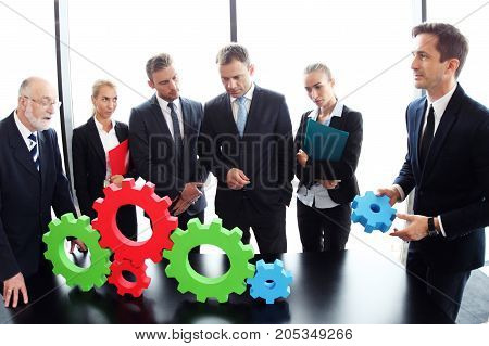 Business people assembling colorful cogwheels teamwork concept