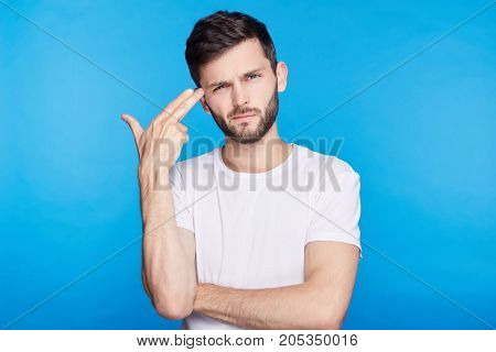 Close up isolated portrait of European young bearded hipster manager bored with work shooting himself with finger gun gesture against blank blue wall background. Human face expressions and emotions.