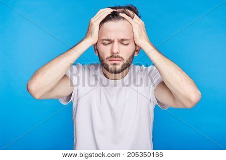 Upset unhappy dark-skinned male student squeezing head with hands writhing in pain suffering from headache after he spent sleepless night preparing for exams. People stress tension and migraine.