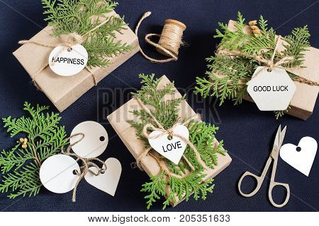 Homemade gift box decoration for Christmas. DIY hobby. Original gift boxes are wrapped in kraft paper tied with twine with twigs of thuja and tags with wishes of happiness love good luck