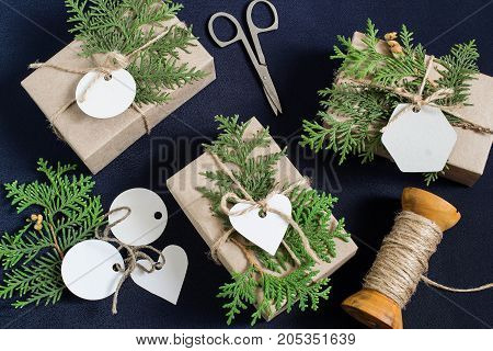 Homemade gift box decoration for Christmas. DIY hobby. Boxes are wrapped in kraft paper tied with twine with twigs of thuja and tags for wishes. Original gift decoration