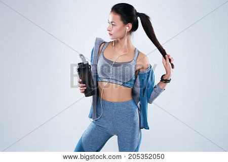 Fitness woman standing in studio over white background with bottle of water and earphones looking away.