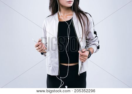 Cropped image of casual sport woman starts training with earphones and mobile telephone in her hands. Standing in studio isolated over gray background