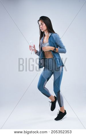 Beautiful sport girl run with bottle of water in earphones and listen to music. Full length of sports woman running in studio over gray background