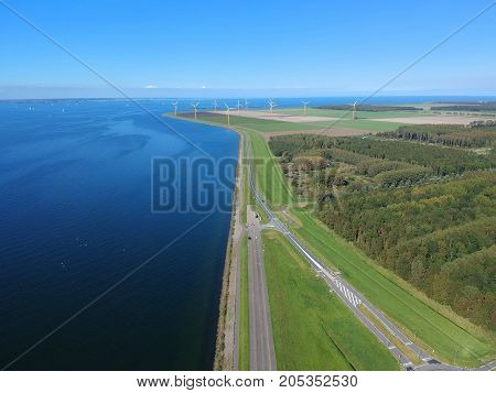 Aerial (drone) view of a Dutch dike and in the polder of Flevoland (Almere Poort), The Netherlands.