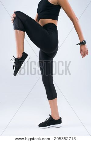 Cropped image of a sportswoman stretching leg while standing isolated over gray background
