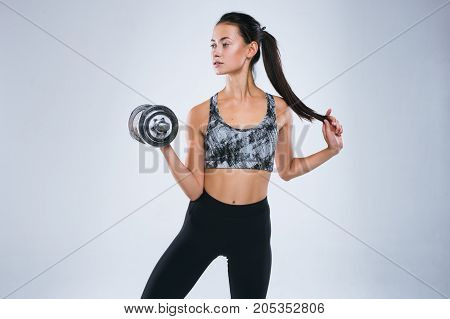 Attractive strong woman holding weight in her hand and posing in sport wear isolated over gray background and looking away