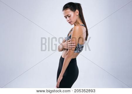 Cropped image of young fitness woman having arm pain while standing isolated over gray background
