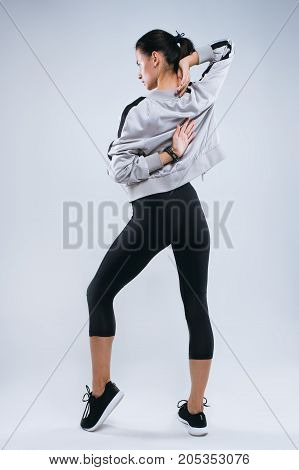 Slim and sport young woman posing and doing sport exercises standing with her back to the camera and stretching arms in studio isolated over gray background