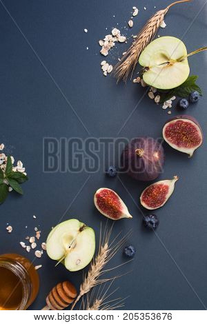 Figs apples honey and wheat on a gray background. View from above