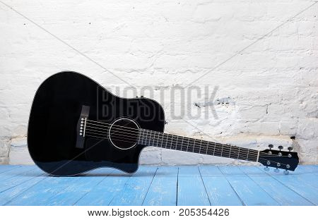 Musical instrument - Black acoustic guitar on a brick background and blue wooden floor.