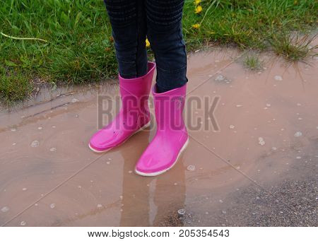 Saverne, Bas-Rhin, France - May 3, 2016: Girl standing in a puddle with pink rubber Dunlop child rain boots.
