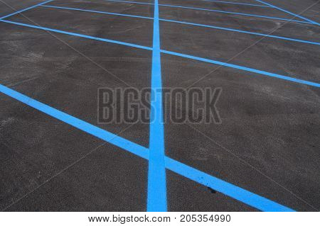 Freshly paved painted parking lots in blue lines.