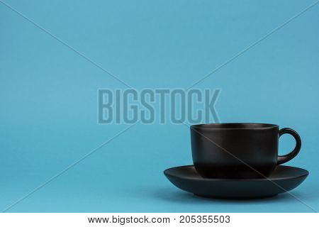 The turquoise background is a black ceramic mug