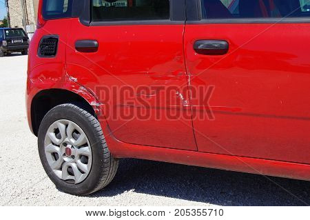 Peschiera del Garda, Italy - August 12, 2017: Red damaged door of a Fiat Panda parked on a public parking lot in the city of Peschiera del Garda. Nobody in de vehicle.
