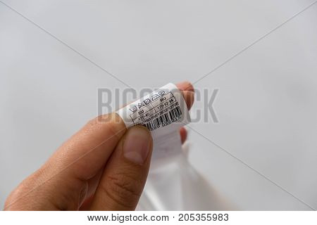 Woman checking the care label. selective focus. Woman's hands holding clothes label with cleaning instructions. lose-up Of Person Reading The Clothing Label Showing Washing Instructions.