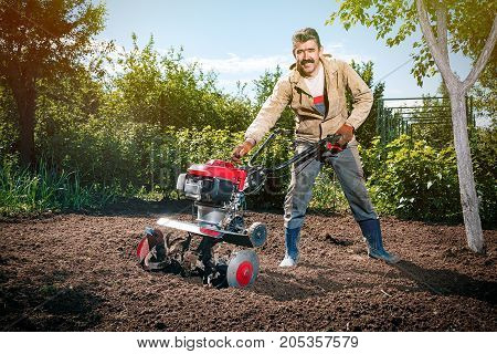 Happy Man Farmer Plows The Land With A Cultivator, Preparing It For Planting Vegetables, On A Sunny