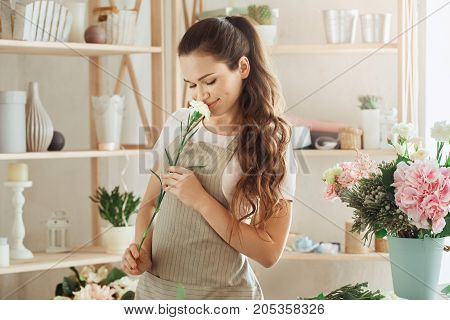 Young female florist working with flowers smell