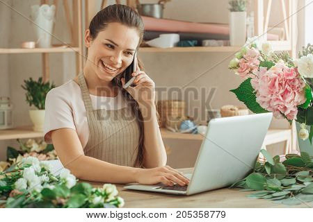 Young female florist working with flowers phone call