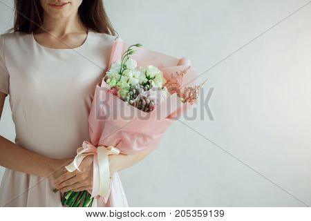 Young female with a bouquet of flowers isolated on white