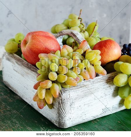 Wooden box with fragrant ripe apples and grapes  Fruit Basket Organic