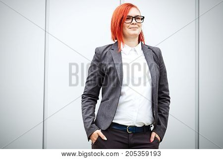 Business Concept Of Success. Serious Successful Woman Boss, In A Suit And Wearing Glasses. With A Pl