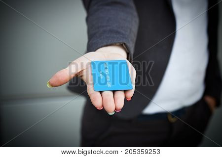 Concept Of Purchases, Banking Services. A Woman In A Suit And Glasses Points And Passes A Credit Car
