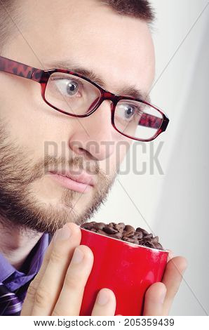 cup with grains of coffee in the hands of man