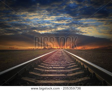 rails going away into the fiery red sunset. View to the rails going away into the dark landscape with fiery red sunset