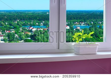 flower-pot on the window-sill of cozy room and view to the country houses