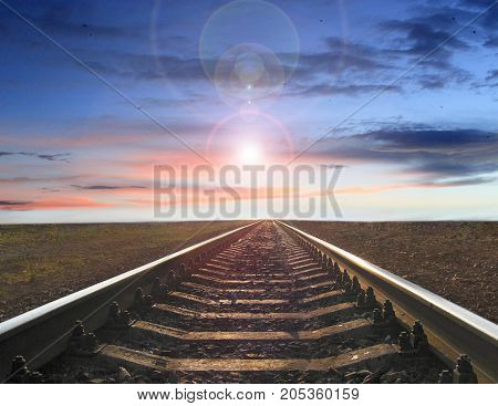 landscape with railway track going away into the sunset and evening star