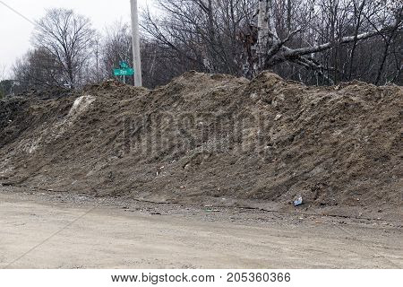 A pile of snow begins to melt, revealing dirt, rocks, and debris, during March, at the intersection of Rice and Shire Streets, in Bay View, Michigan.