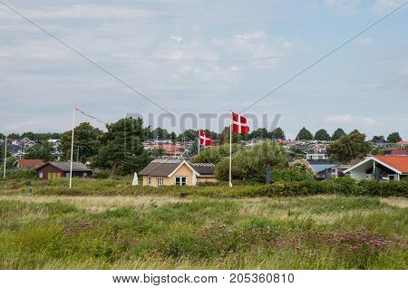 Summer Homes And Danish Flag In Front Of Vacation Homes In Karrebaeksminde In Denmark