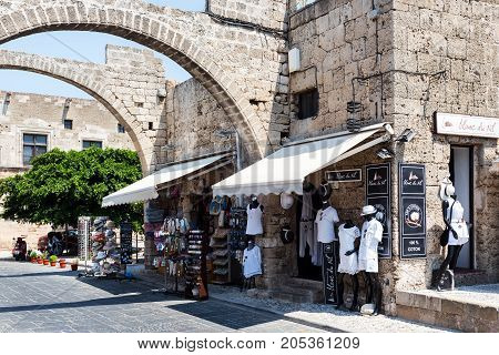 RHODES, GREECE - AUGUST 2017: Ancient arch in old wall of Rhodes town with small shops under it in Rhodes town on Rhodes island, Greece